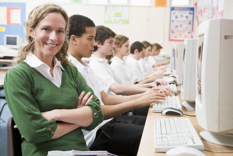 Fileira dos alunos que estudam em computadores imagens de stock royalty free