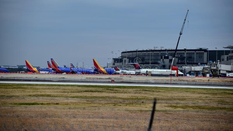 Fileira dos aviões do sudoeste e do Delta Airlines estacionados em suas portas imagem de stock