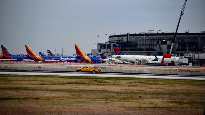 Fileira dos aviões do sudoeste e do Delta Airlines estacionados em suas portas fotografia de stock