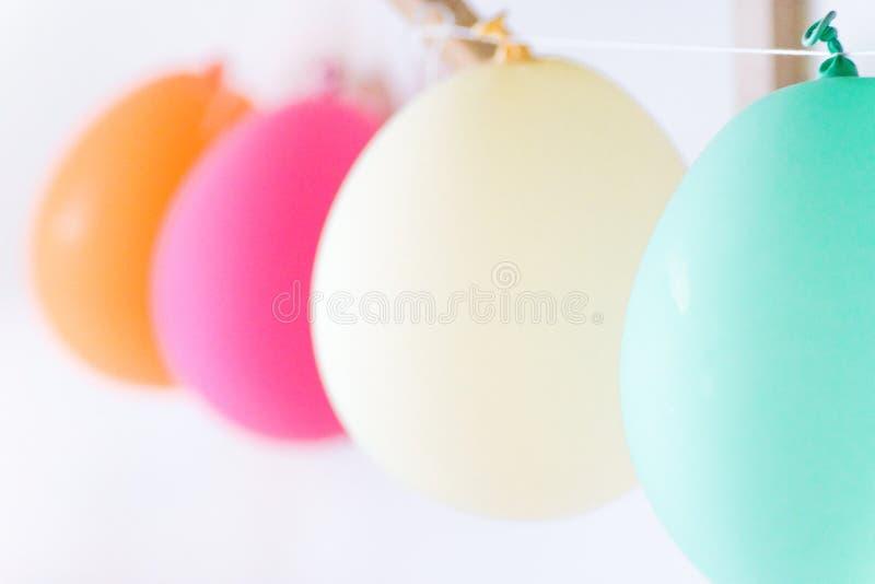 Fileira dos balões de ar alaranjados cor-de-rosa brancos de turquesa que penduram na sala das crianças Divertimento da celebração imagens de stock
