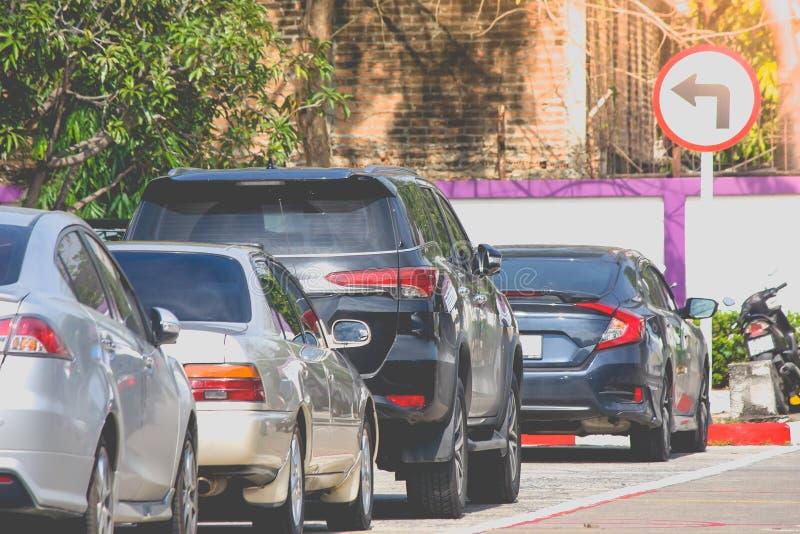A fileira dos carros estacionou no assoalho concreto no parque de estacionamento do carro com luz solar no fundo fotografia de stock royalty free