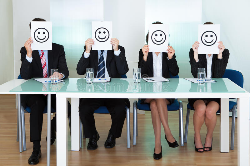Fileira dos executivos empresariais com faces do smiley imagem de stock royalty free