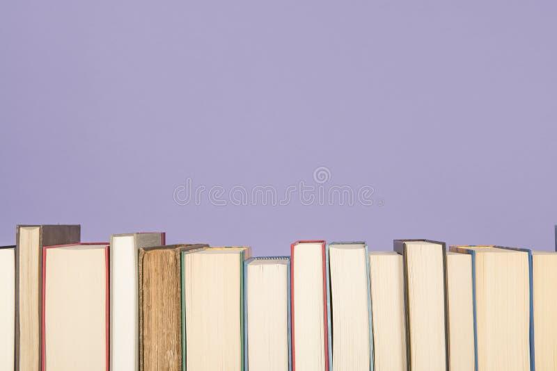 Fileira dos livros em um fundo do roxo da alfazema imagens de stock