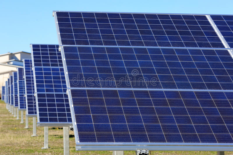 Fileira dos painéis solares em um campo fotografia de stock