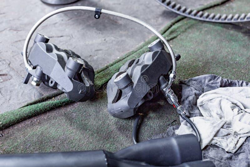 A fileira dos parafusos e das ferramentas da chave em um assoalho na oficina próximo reparou o motor velho da bicicleta ou da mot foto de stock