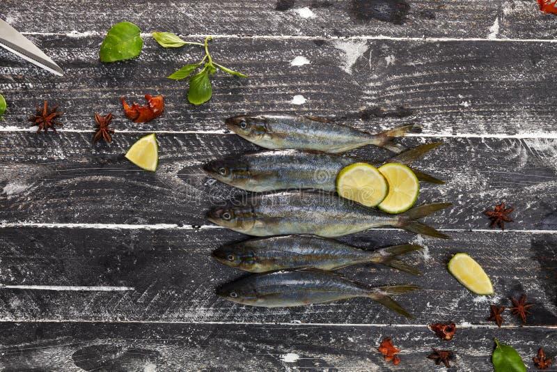 Fileira dos peixes no fundo de madeira preto, conceito cozinhando o fundo imagem de stock royalty free