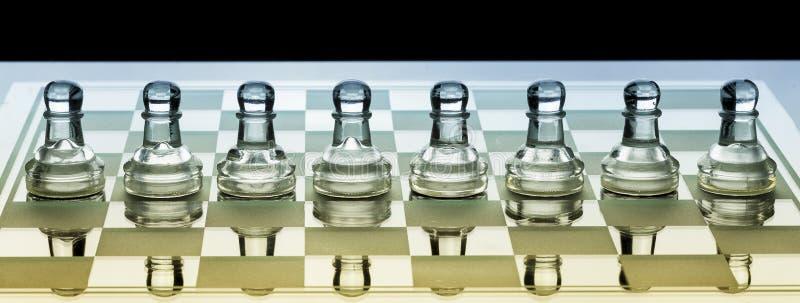 Fileira dos penhores de vidro da xadrez em uma placa com máscara azul e alaranjada fotos de stock royalty free