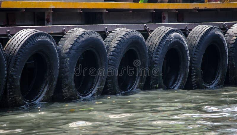 Fileira dos pneus de carro pretos usados como amortecedores do barco no cais fotografia de stock royalty free