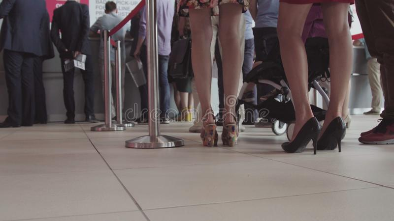 Fileira dos povos que esperam em um aeroporto Pés dos povos na linha no aeroporto fotografia de stock