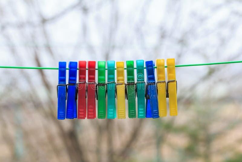 Fileira dos pregadores de roupa coloridos que penduram em uma corda verde em um gerden imagens de stock