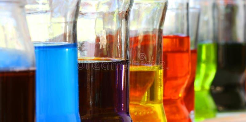 Fileira dos vidros com líquidos coloridos fotografia de stock
