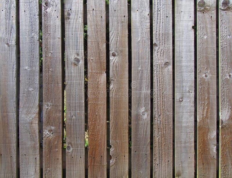 A fileira espaçou uniformemente as pranchas marrons ásperas da madeira usadas como uma cerca do jardim fotografia de stock royalty free