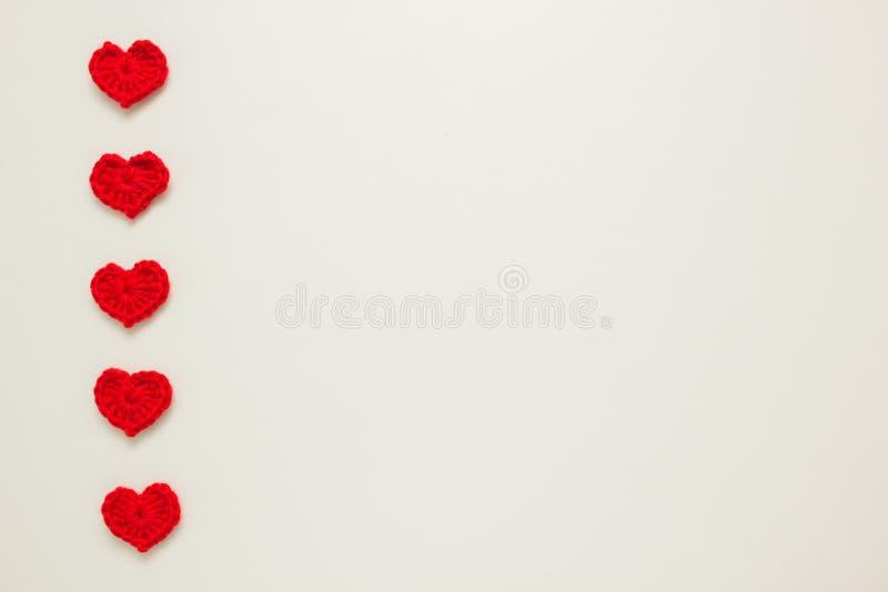 Fileira vertical de corações feitos malha vermelho fotos de stock royalty free