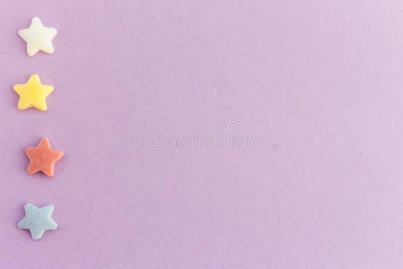 Fileira vertical de estrelas coloridas no fundo roxo com espaço da cópia Cartão brilhante fotografia de stock