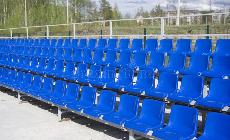 Fileiras azuis, vermelhas, brancas dos assentos no estádio fotografia de stock