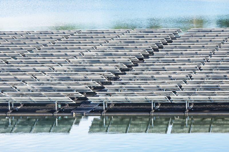 Fileiras das células solares ou do photovoltaics na água no lago da central elétrica fotos de stock royalty free