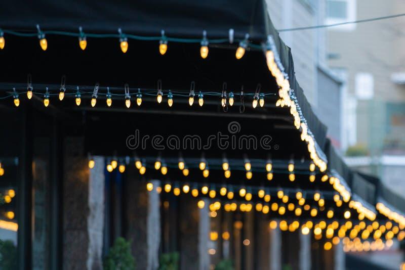 Fileiras das luzes de Natal que penduram das barracas imagens de stock royalty free
