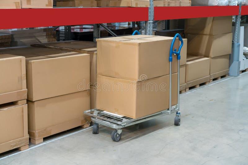 Fileiras das prateleiras com caixas e carros do armazenamento no armazém imagens de stock