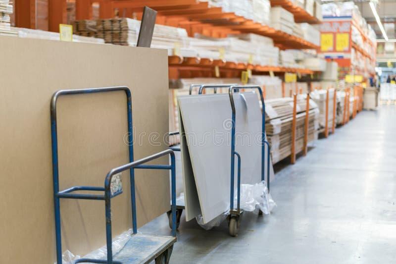 Fileiras das prateleiras com caixas e carros do armazenamento no armazém moderno fotos de stock royalty free