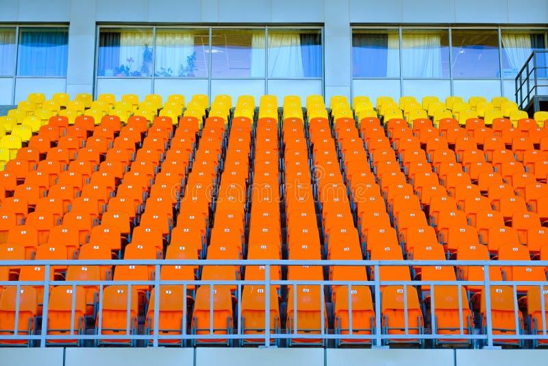 Fileiras de assentos plásticos amarelos e alaranjados vazios em um estádio fotos de stock