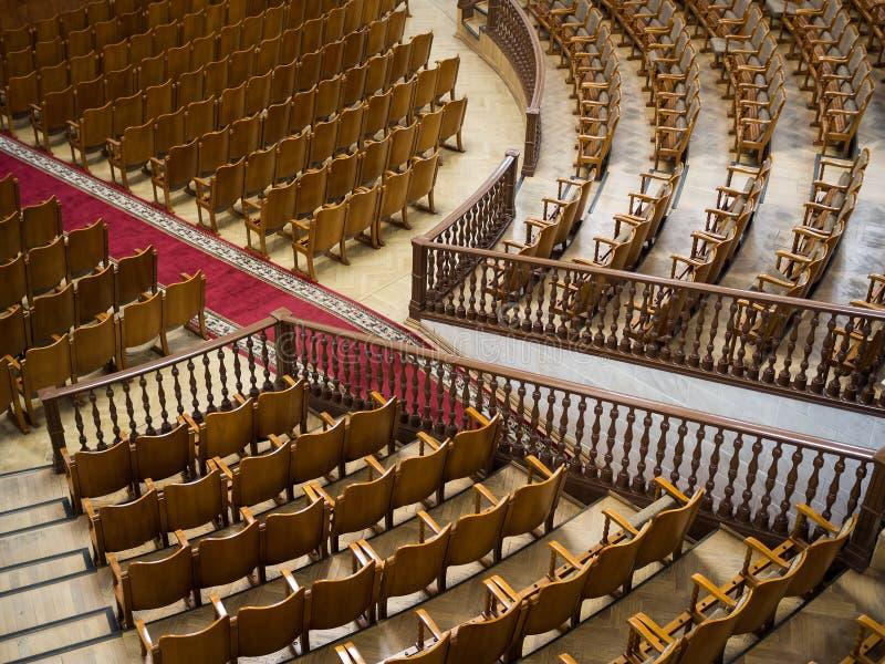 Fileiras de cadeiras de madeira em um grande salão foto de stock