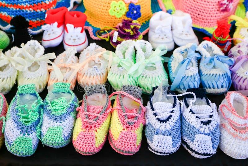 Fileiras de sapatas de bebê feitas malha coloridas no preto fotos de stock