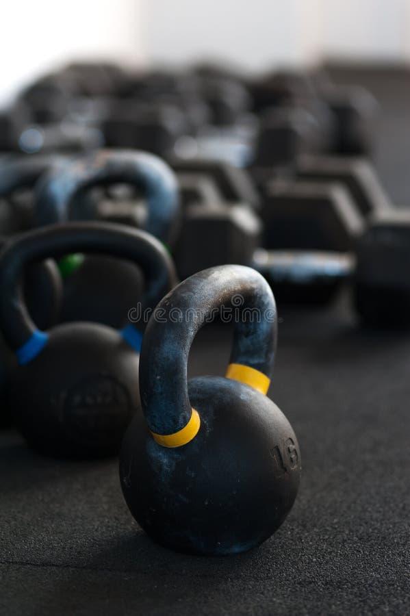 Fileiras de sinos e de pesos da chaleira no assoalho do gym imagem de stock royalty free