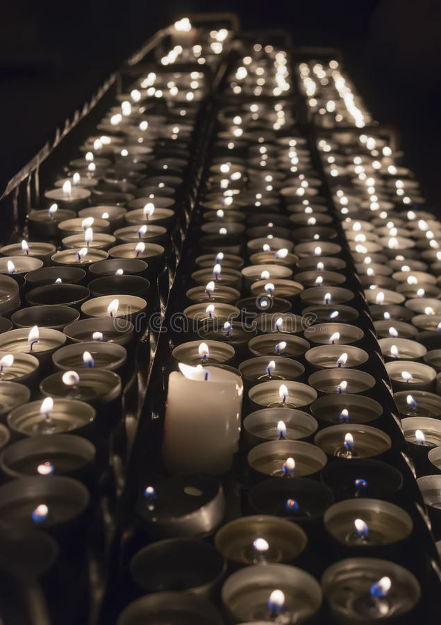 Fileiras de velas ardentes dentro de uma igreja imagem de stock