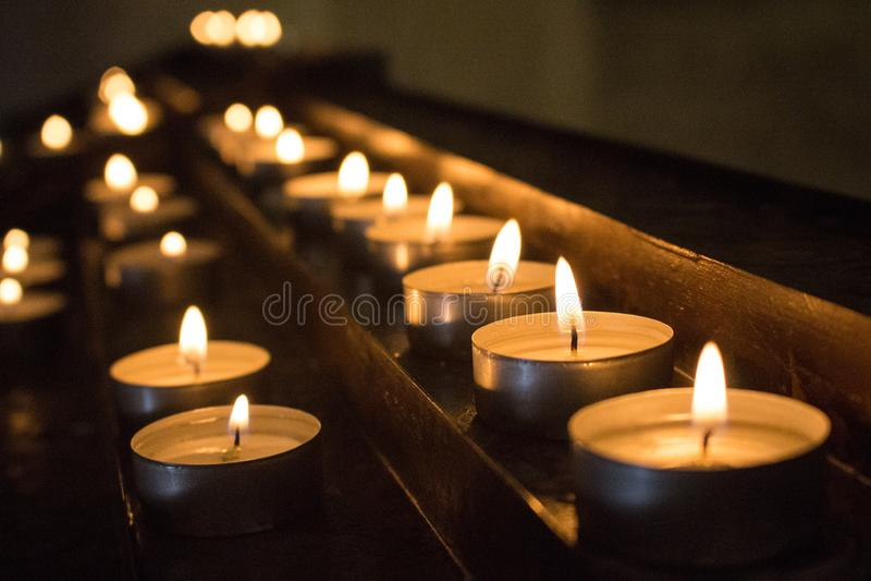 Fileiras de velas de incandescência na escuridão Velas com falme ardente Decoração da igreja Fundo da religião e da fé fotografia de stock royalty free