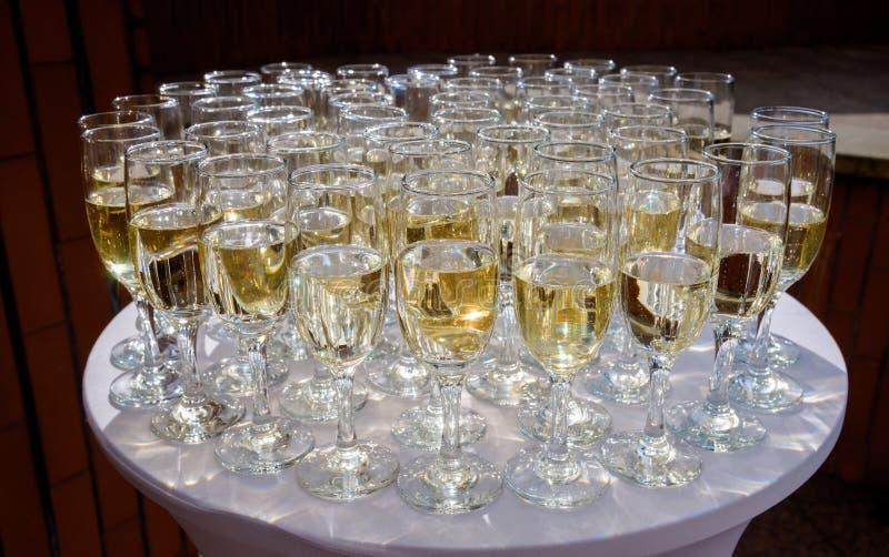 Fileiras de vidros do champanhe e de vinho para o partido e o casamento imagem de stock royalty free
