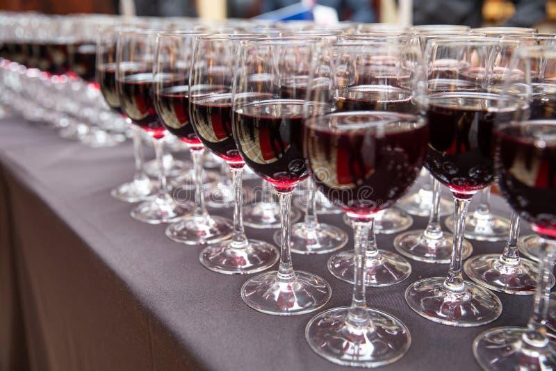Fileiras de vidros de vinho tinto para o partido e o casamento foto de stock