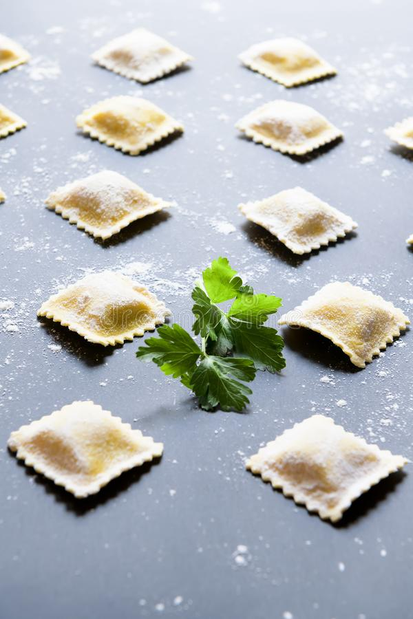 Fileiras do ravioli caseiro cru em um fundo escuro fotos de stock