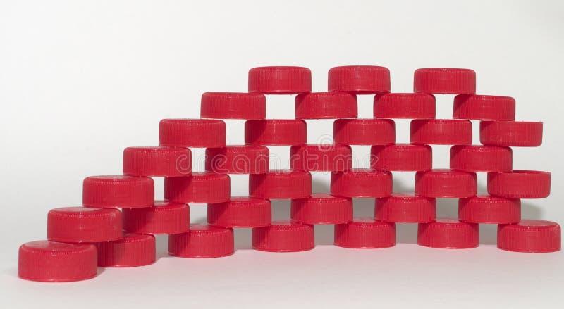 Fileiras dos tampões de garrafa plásticos com nervuras vermelhos que colocam em se fotografia de stock