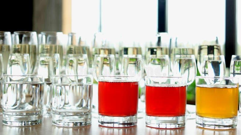 Fileiras dos vidros com bebidas alcoólicas na tabela fotos de stock