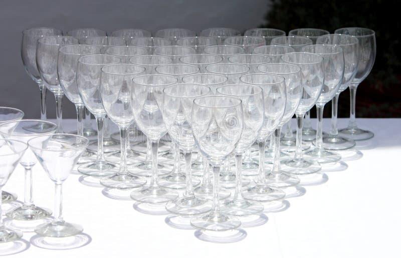 Fileiras dos vidros de vinho que esperam para ser usado foto de stock