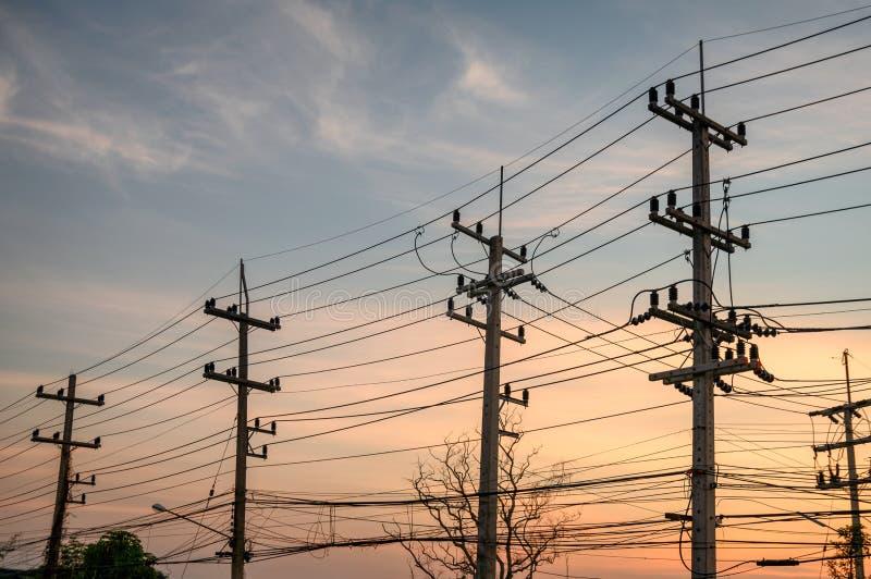 Fileiras rurais do polo da eletricidade com rede dos fios no por do sol imagem de stock
