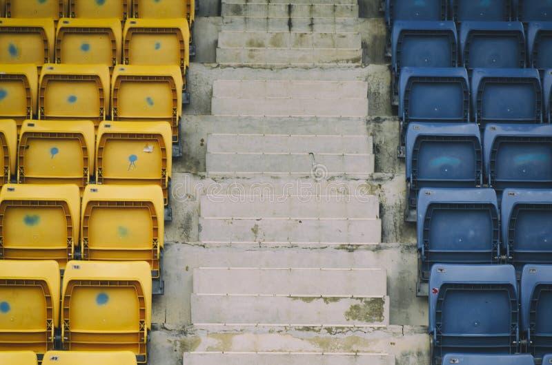 Fileiras vazias com assentos azuis e amarelos no estádio do ar livre foto de stock