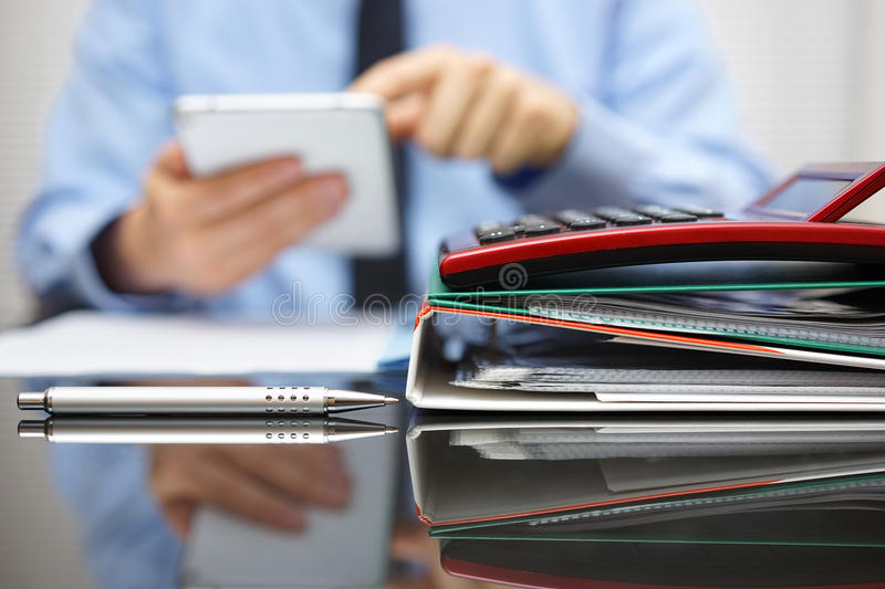 Files and folders and businessman in background with tablet pc i royalty free stock photo