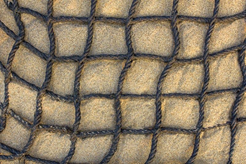 Filet ? carreaux ?pais noir de c?ble sur la vue sup?rieure de sable l?ger Texture de surface approximative images libres de droits