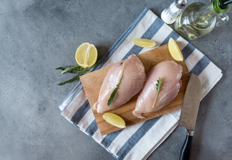 Filet cru de poulet avec l'arugula sur la planche à découper et la serviette, le couteau, la bouteille d'huile et le dispositif t images libres de droits