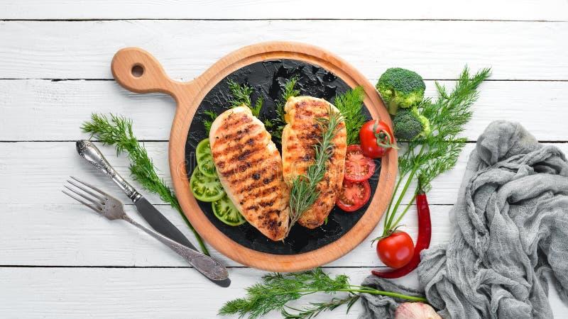 Filet cuit au four de poulet avec des herbes et des épices sur un fond en bois blanc photo libre de droits