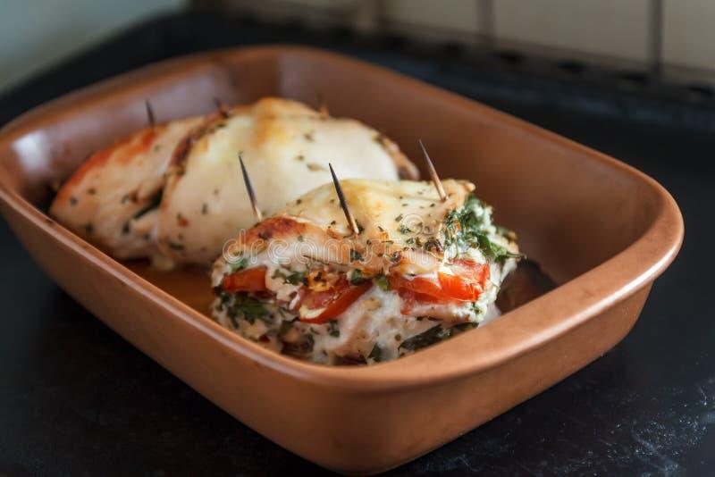 Filet cuit au four de volaille bourré du fromage à pâte molle, des tomates et de l'herbe photo stock