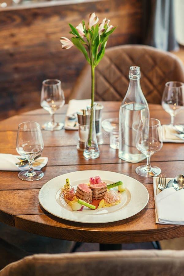 Filet délicieux de porc avec des pommes de terre mâche et légumes servis du plat blanc avec de la sauce, photographie de produit  image stock