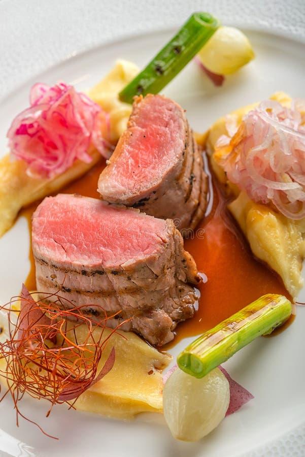 Filet délicieux de porc avec des pommes de terre mâche et légumes servis du plat blanc avec de la sauce, photographie de produit  photo stock