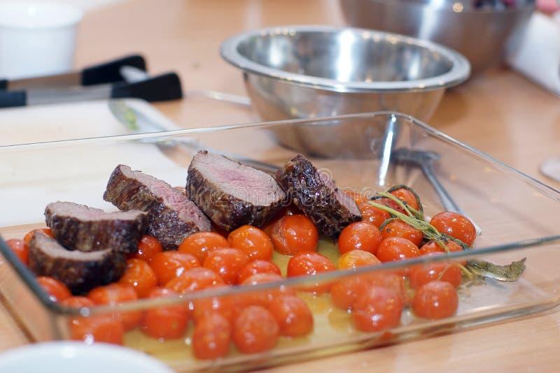 Filet de boeuf coupé en tranches avec les tomates-cerises cuites au four avec de la sauce blanche images stock