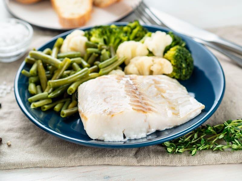 Filet de morue bouilli de poisson de mer avec des légumes du plat bleu, W gris photographie stock