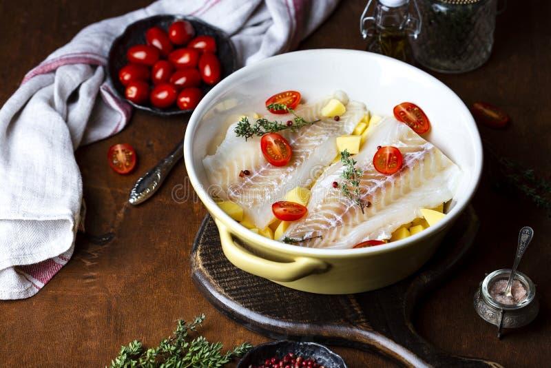 Filet de morue cru avec des pommes de terre et des tomates dans le plat de cuisson images stock