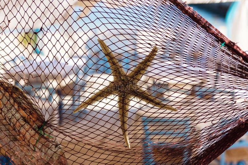 Filet de pêche décoré des étoiles de mer et du coquillage au restaurant grec traditionnel par la plage et le port de pêche photographie stock