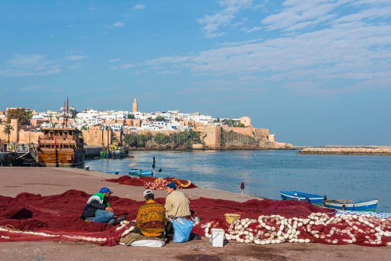 Filet de pêche de fixation de Fishermans dans le port de pêche de Rabat le Maroc rabat image stock