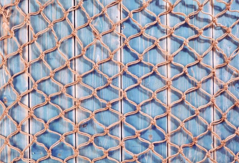 Filet de pêche naturel de corde au-dessus des planches en bois bleues photographie stock libre de droits